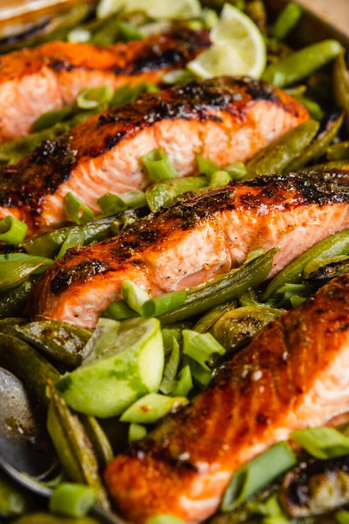 salmon fillet surrounded by snap peas