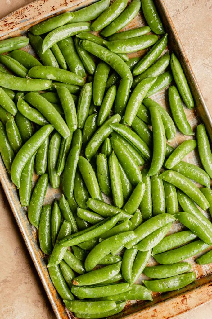 fresh snap peas coated in oil on a sheet pan