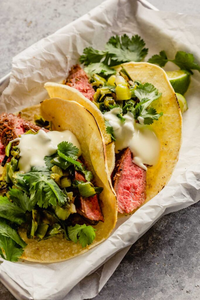 steak tacos in small sheet pans lined with parchment paper.