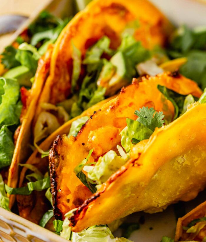 taco made with yellow corn tortilla, tomato filling, with melted and browned cheese and topped with lettuce and avocado