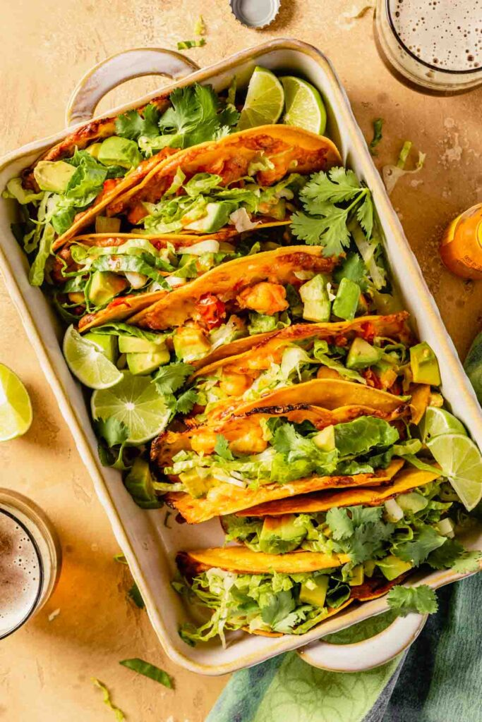 Tacos filled with an orange-colored filling and topped with shredded lettuce, avocado and lime wedges arranged in a baking dish