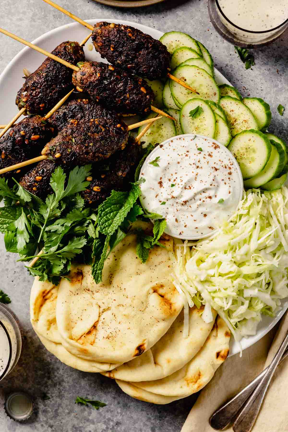 large white platter full of ground lamb skewers, shredded cabbage, sliced cucumber, herbs, and naan bread