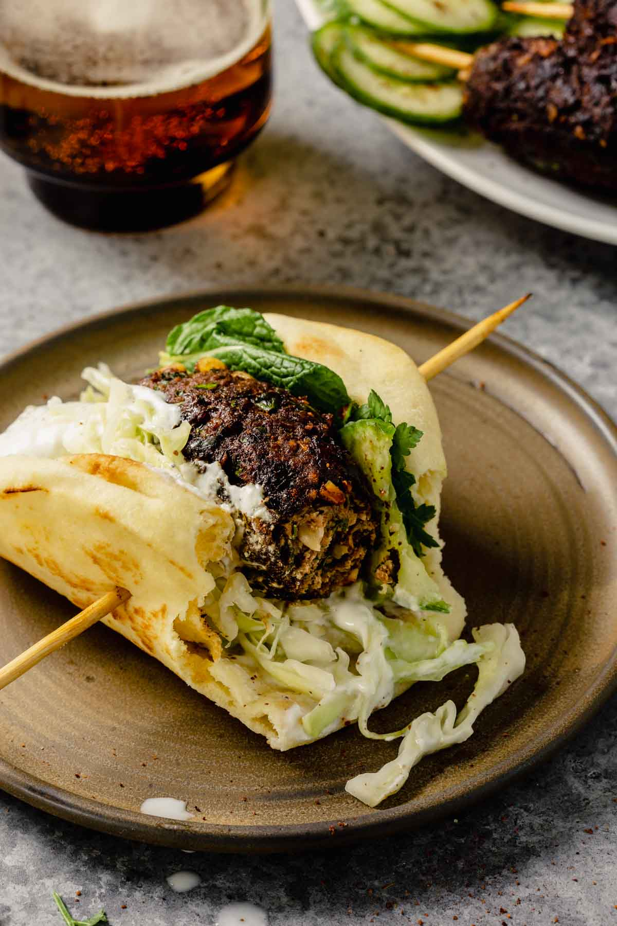 lamb kofta on a piece of naan bread topped with shredded cabbage, yogurt sauce, herbs and cucumber