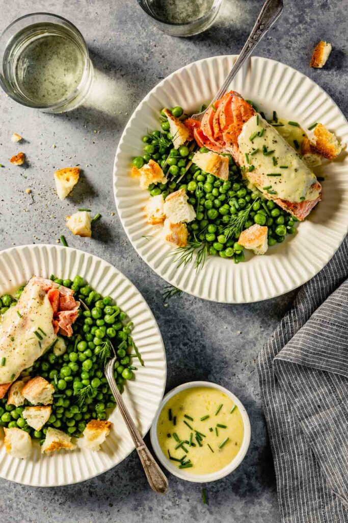 white scalloped plates filled with green peas, salmon topped with butter, croutons and herbs. Glasses of wine set around