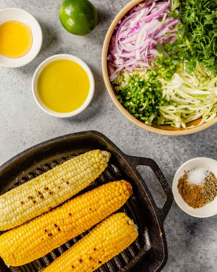 a bowl filled with shredded green cabbage, sliced red onion, cilantro and jalapeno. Corn charred in a grill pan and honey, olive oil and lime set off to the side