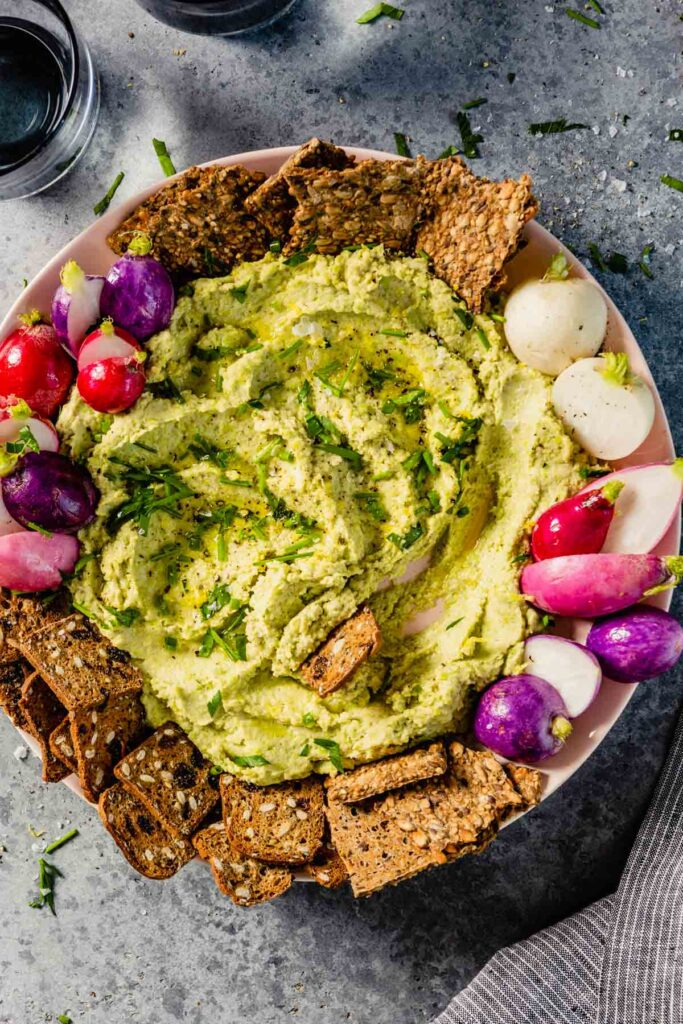 green hummus on a large round plate with radishes and crackers set around it