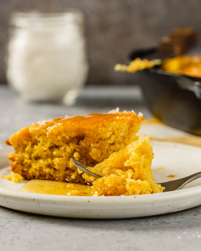 a piece of cornbread on a white plate with honey dripping down it