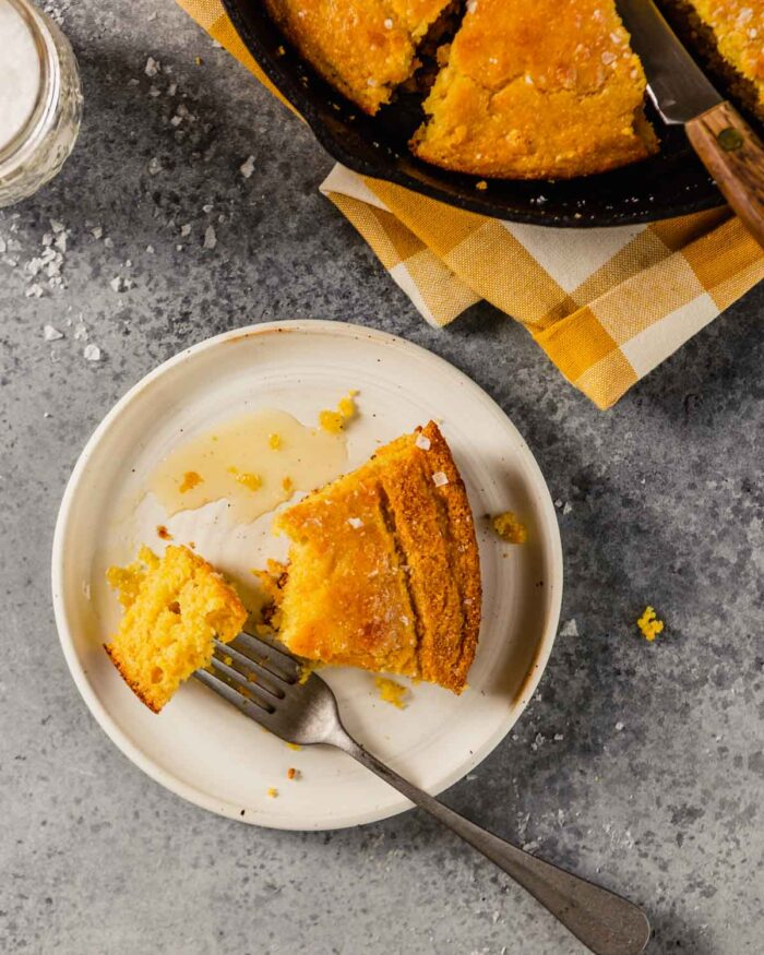 a piece of cornbread on a white place with a skillet of cornbread off to the side