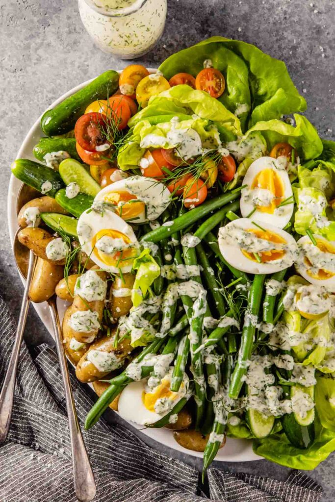large white platter filled with butter lettuce, blanched green beans, fingerling potatoes, halved cherry tomatoes, mini cucumbers, hard boiled eggs and a creamy ranch dressing