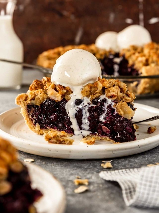 piece of blueberry pie on a white plate with a scoop of melty vanilla ice cream on top