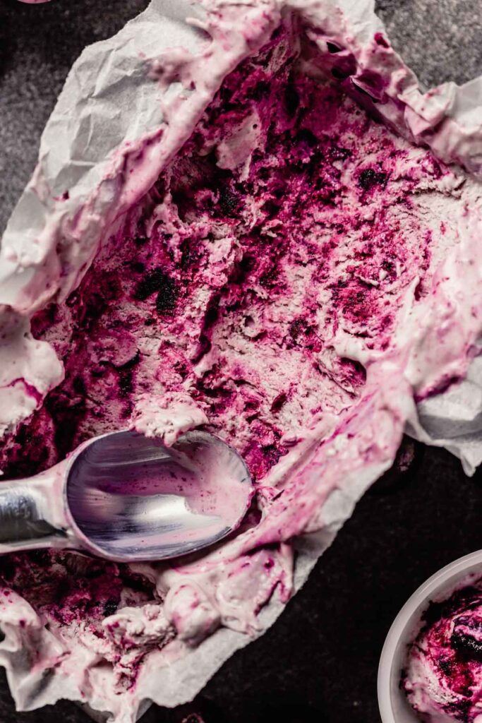swirled cherry ice cream in a loaf pan with scoops taken out and placed in small white bowls