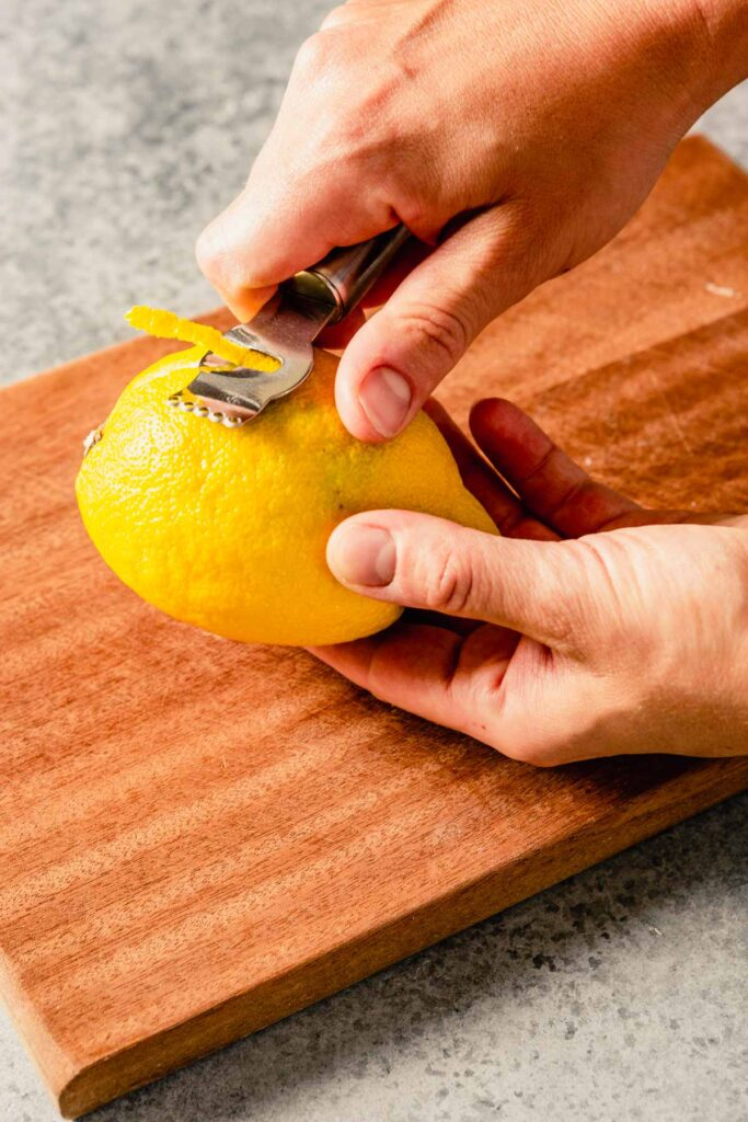 two hands peeling a lemon using a channeling knife set over a wood cutting board