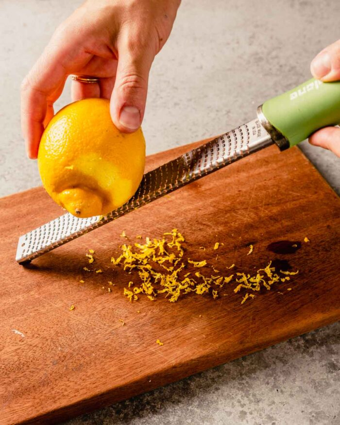 two hands zesting a lemon using a microplane