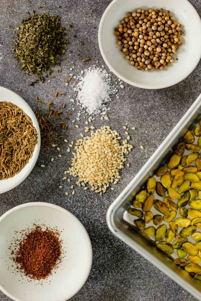 pistachios and spices measured out and set on a table in small white bowls