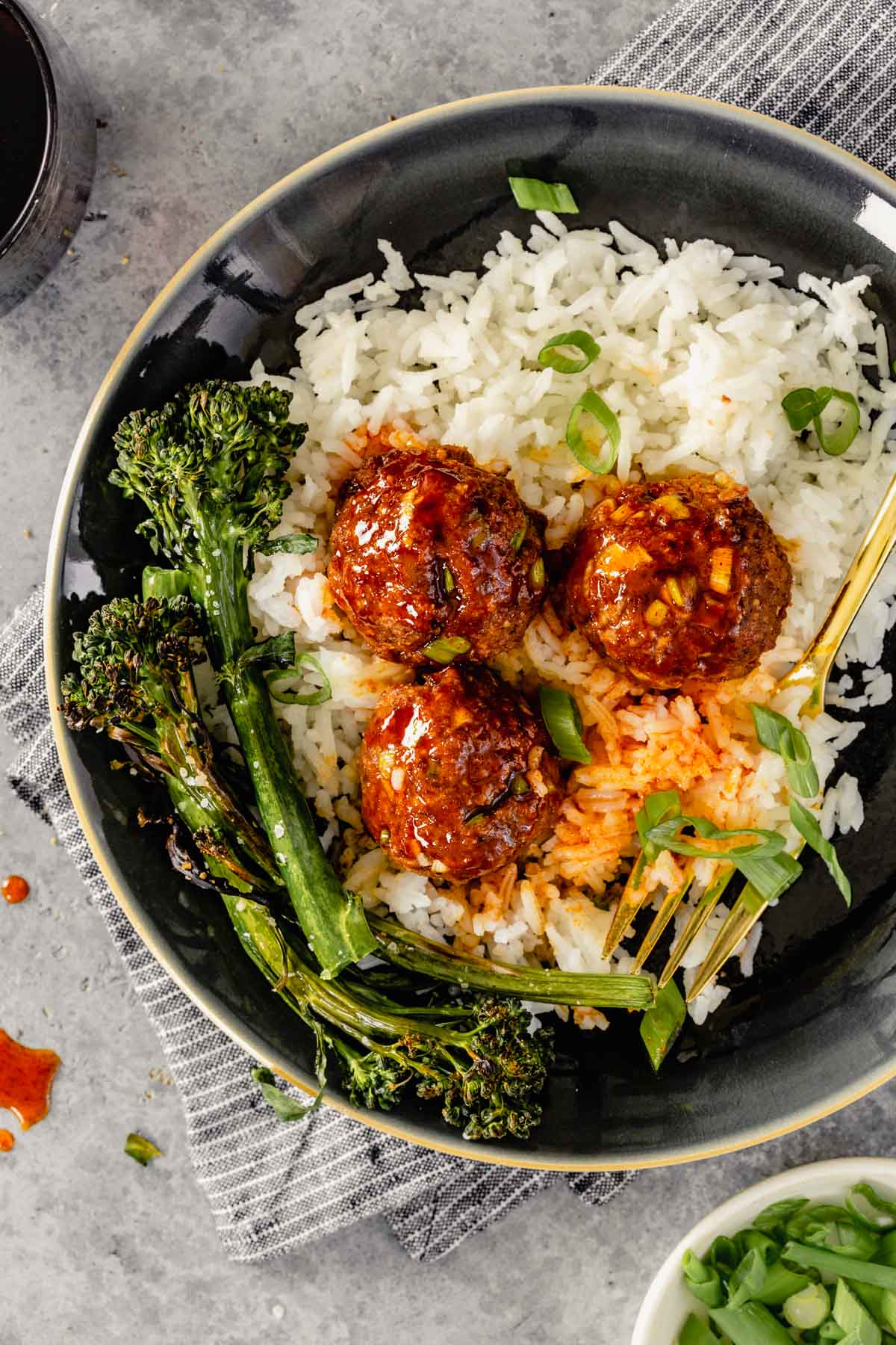 glazed meatballs on a plate of white rice with charred broccolini on the side
