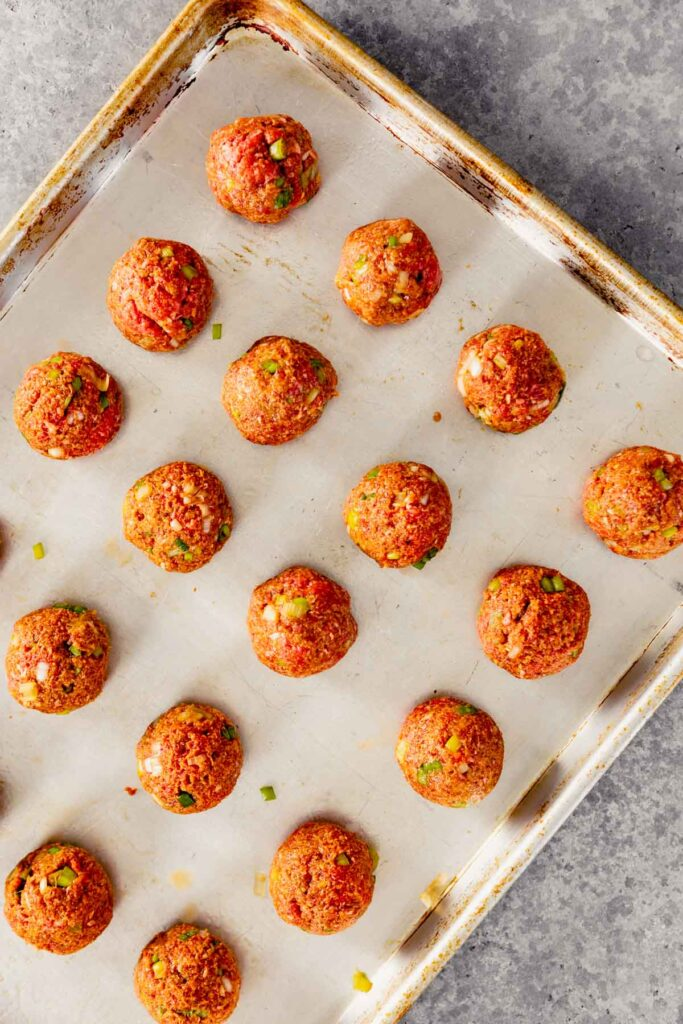 un-cooked meatballs on a baking sheet