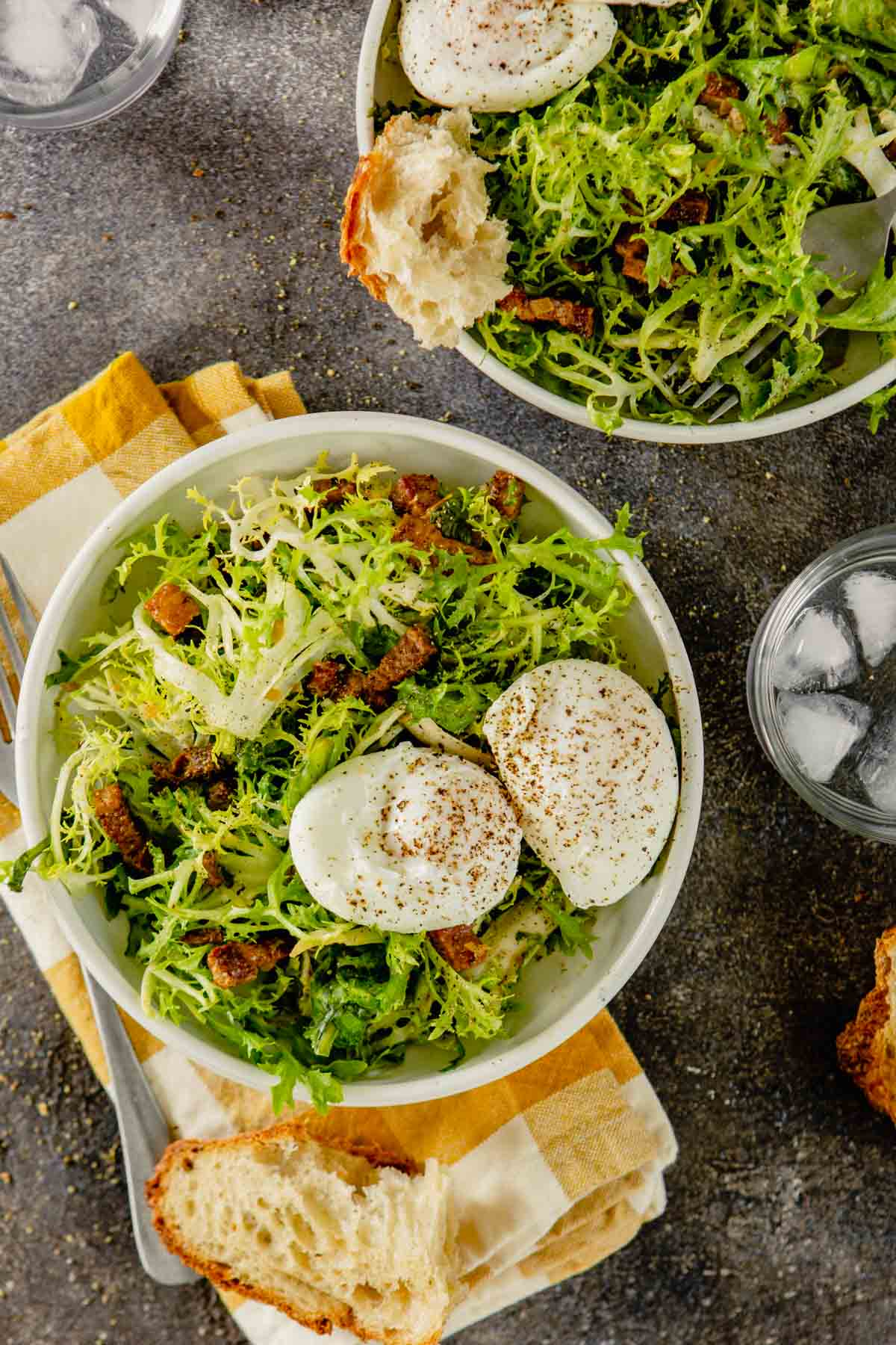 salad in white bowl with bacon lardons and poached eggs