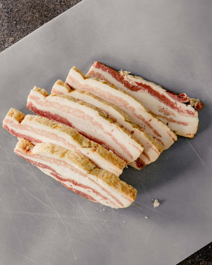 slab bacon sliced into thick strips on a plastic cutting board
