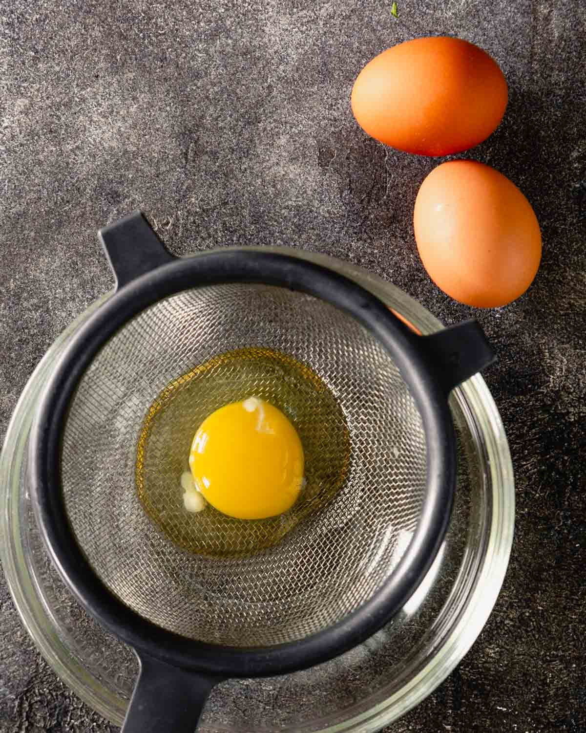 egg draining in a fine mesh sieve set over a glass bowl