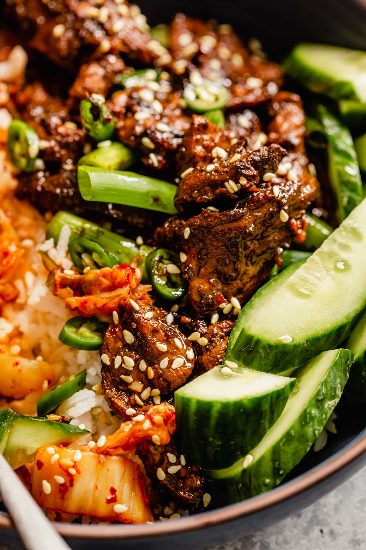 close up image of pork bulgogi in a bowl with rice and sliced cucumber