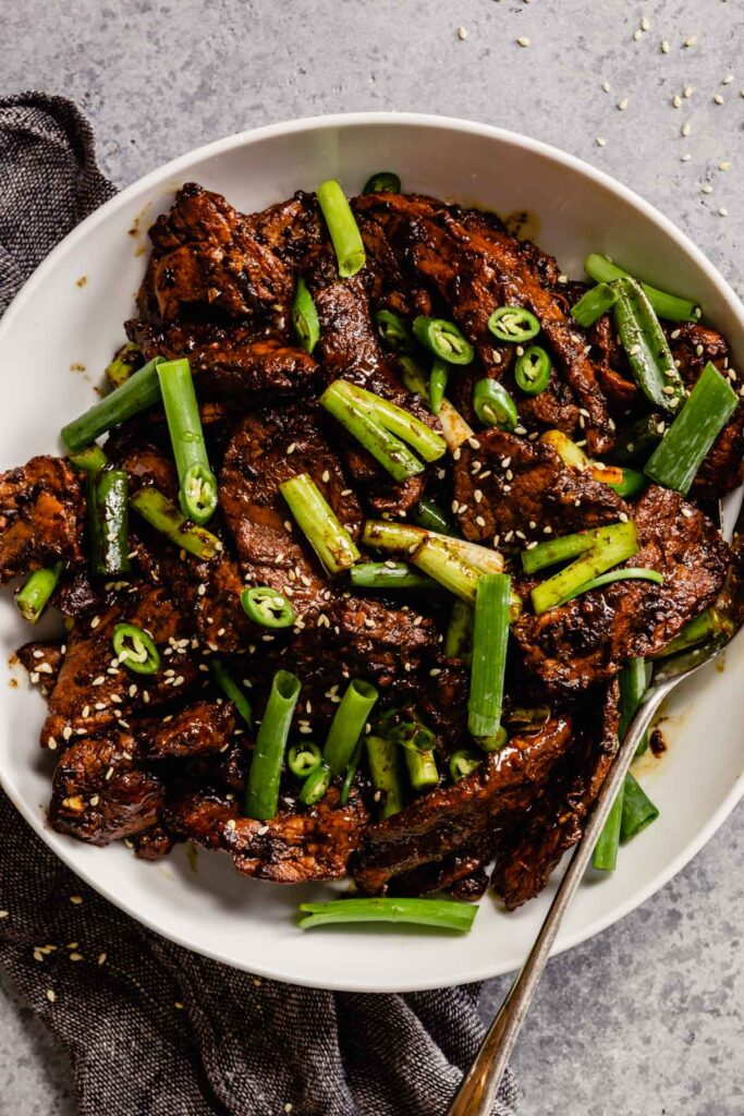 pork bulgogi in a large white bowl with large pieces of green onion and serrano