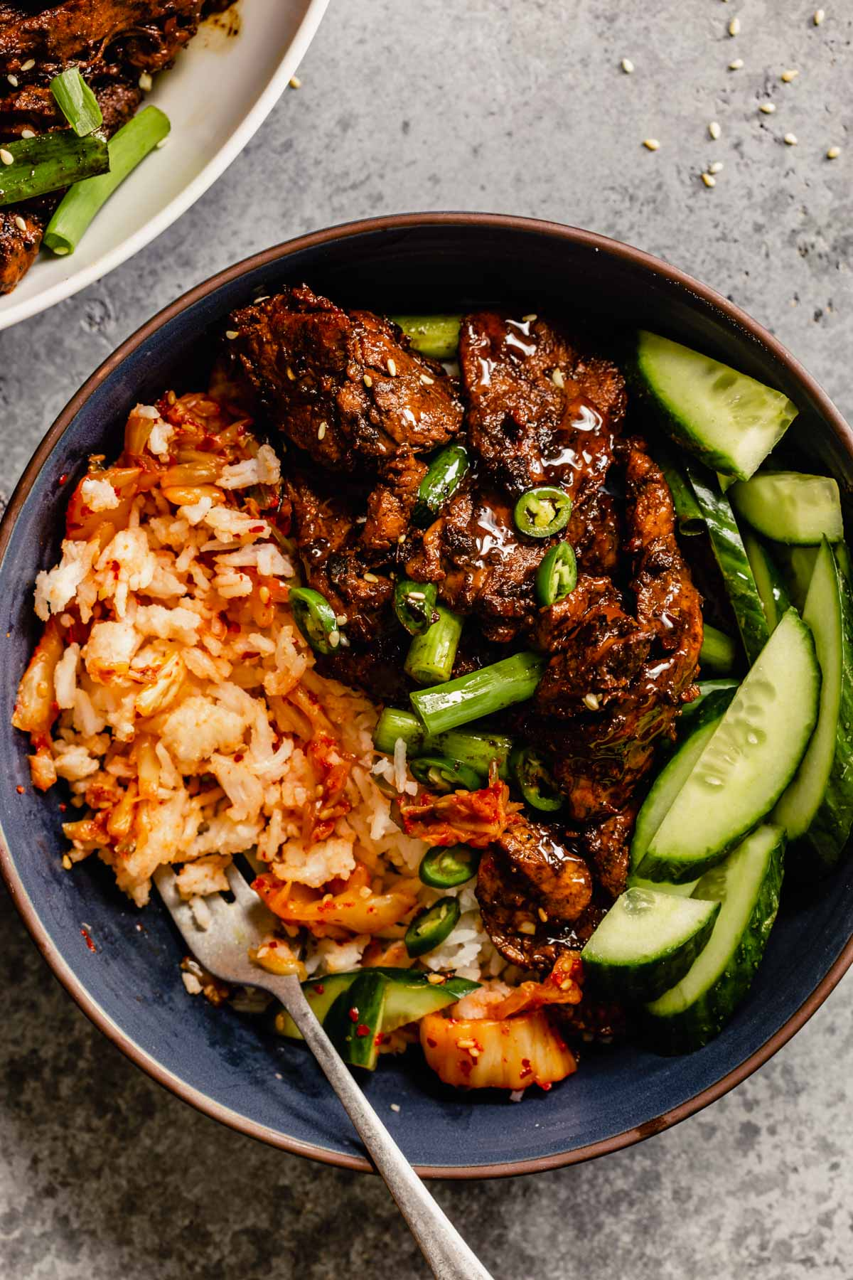 pork bulgogi in a blue dusty bowl with rice and sliced cucumber