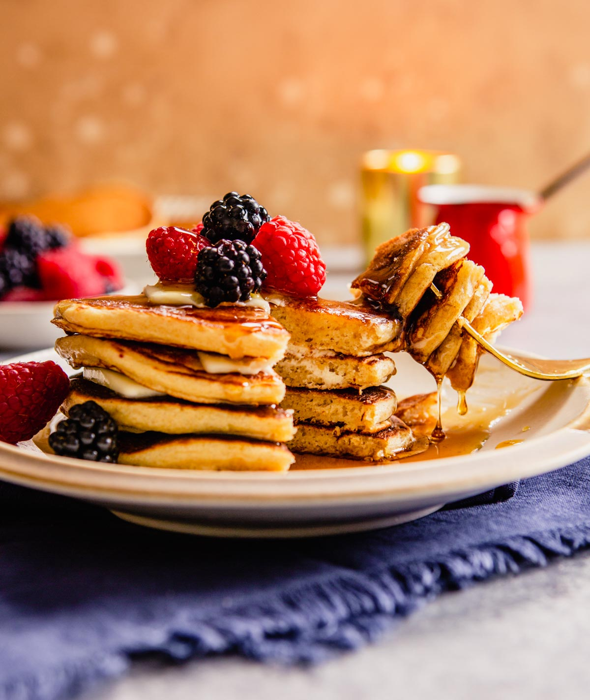 whole wheat pancakes stacked on a plate with berries on top and maple syrup dripping down