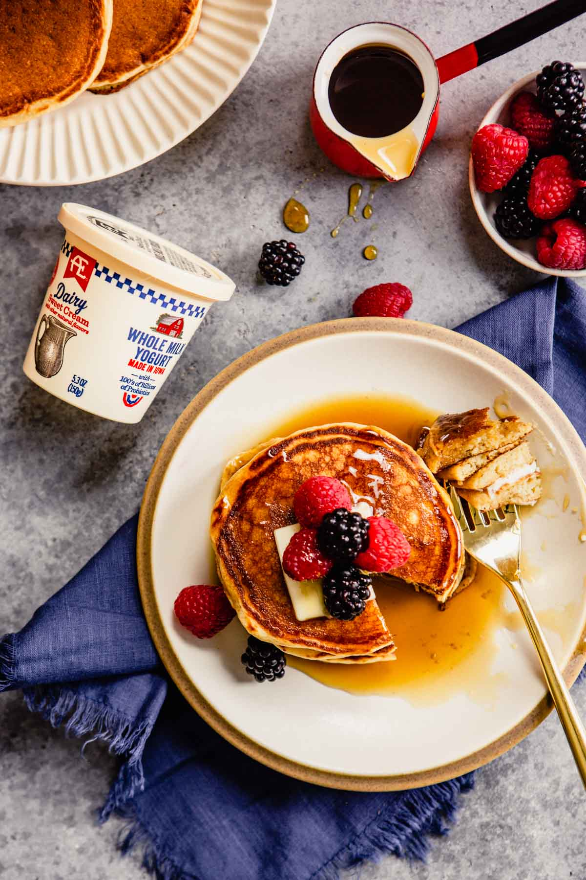 yogurt pancakes on a plate topped with berries and maple syrup