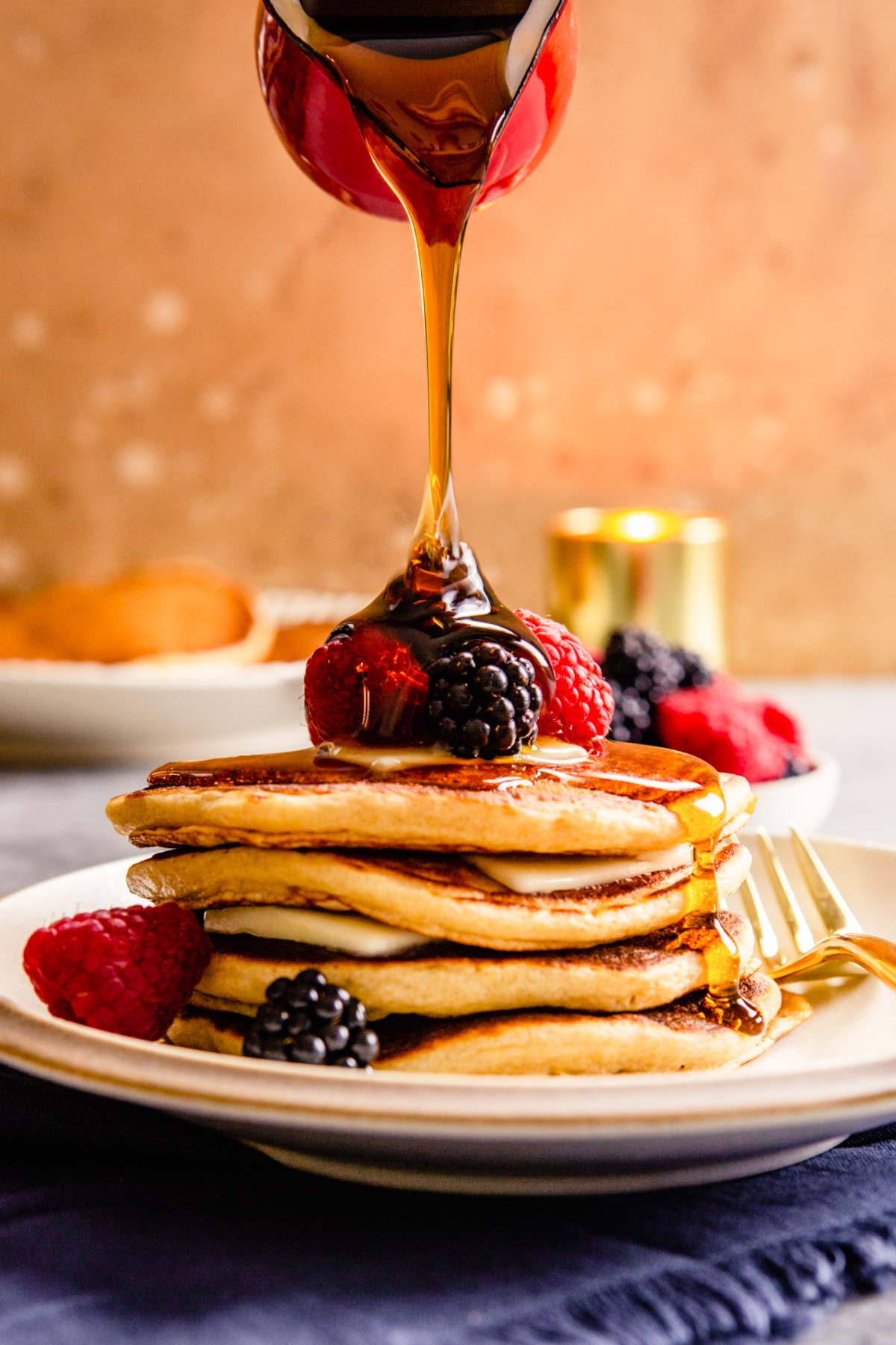 yogurt pancakes stacked on a plate with berries on top and maple syrup dripping down