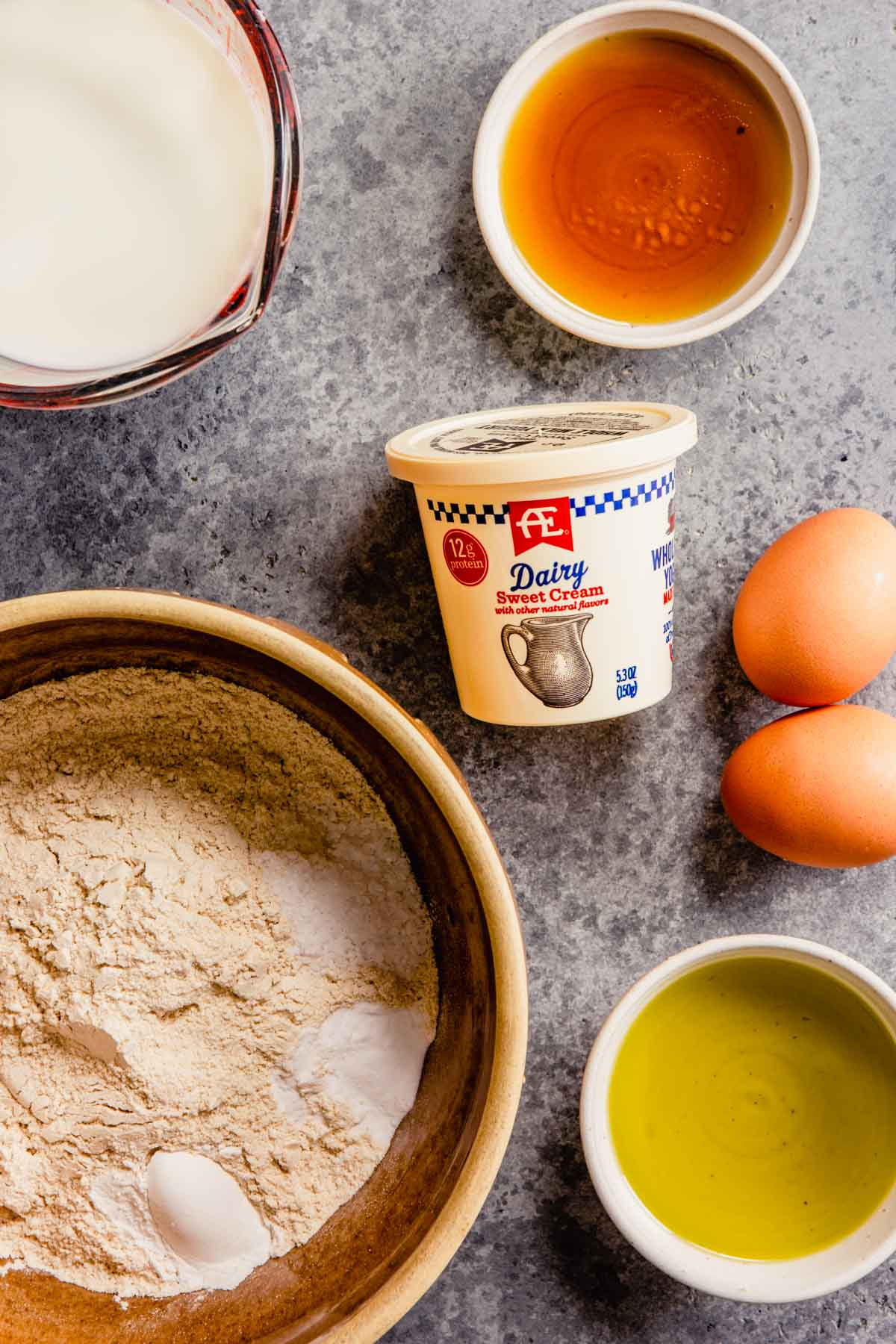 ingredients needed for yogurt pancakes (eggs, oil, flour, yogurt, maple syrup and milk) measured out and set on a counter