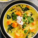 shallow white bowl set on a dark blue plate filled with a yellow-colored curry soup with chunks of sweet potato, kale, ground pork and chickpeas. topped with cilantro, yogurt, and red pepper flakes.