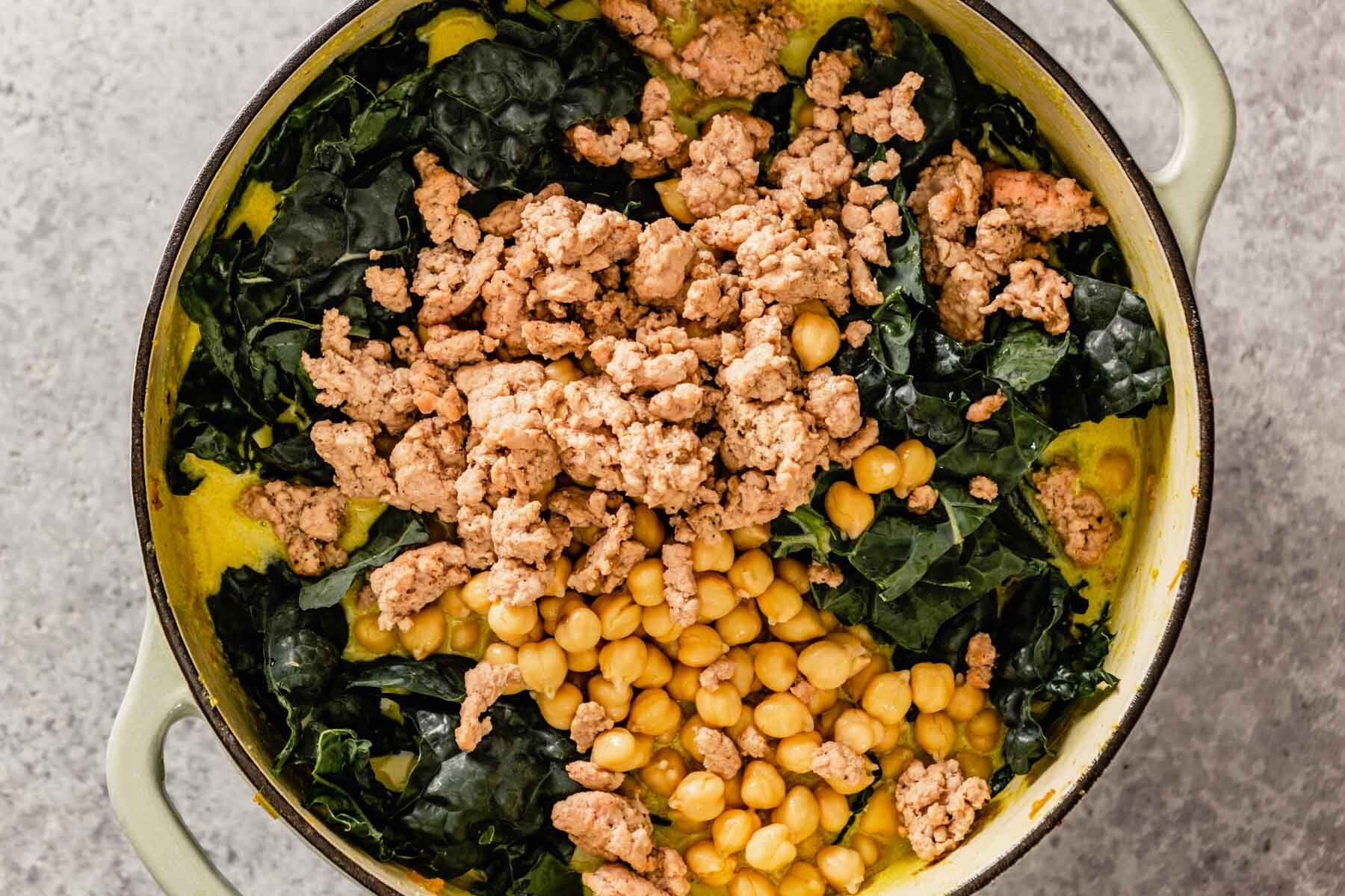 chickpeas, kale, and cooked ground pork added to a large Dutch oven